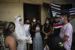 Relatives and friends of the late Eldon Cascais talk to a SOS Funeral worker wearing protection equipment amid the new coronavirus pandemic in Manaus, Brazil, Sunday, May 9, 2020